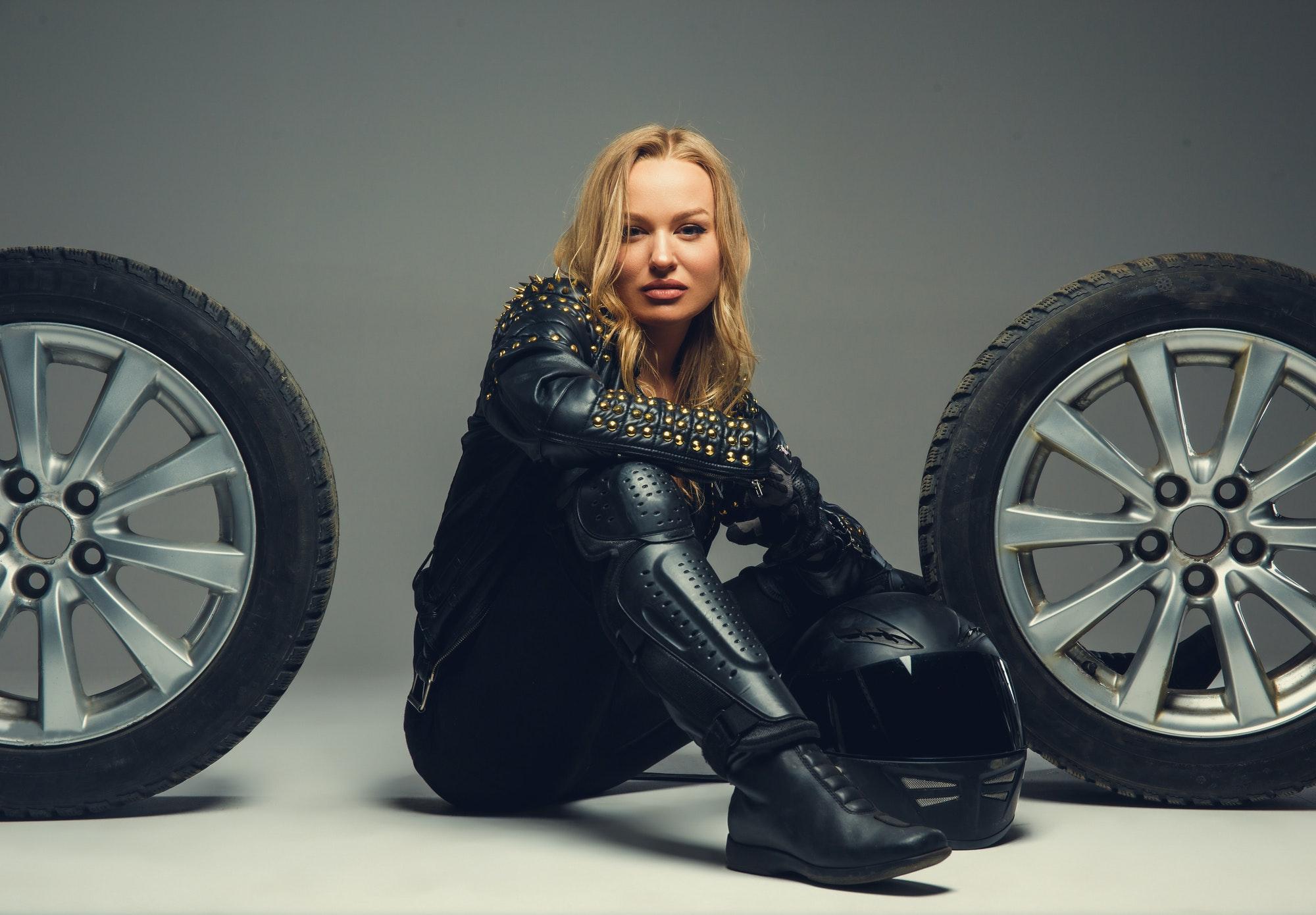 Female with motorcycle helmet sitting between two car wheels.