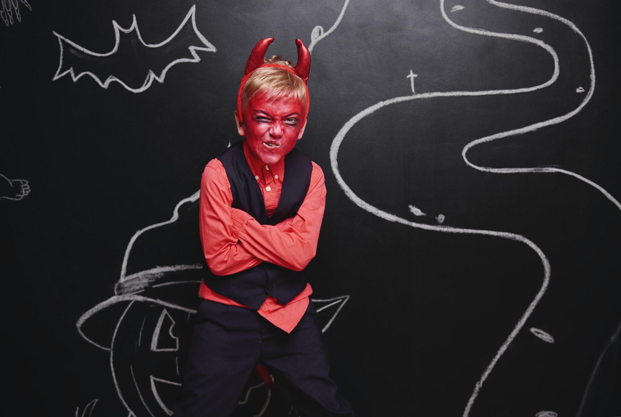 Kid celebrating Halloween in devil costume